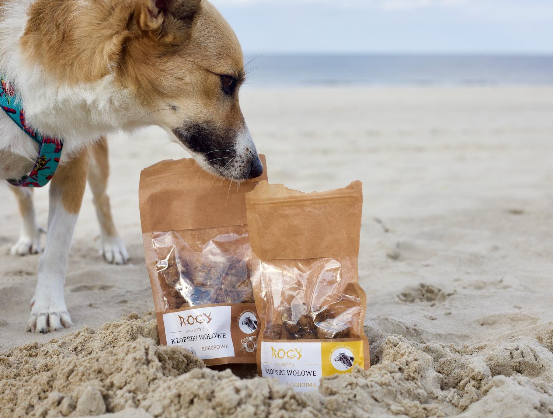 W piasku na plaży stoją dwa opakowania przysmaków dla psów marki Rogy. Zagląda do nich piesek