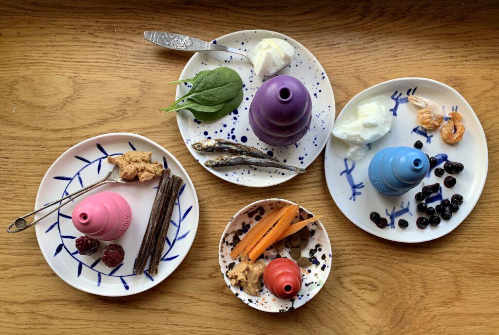 cztery talerzyki na stole pokazują przykładowe przepisy na kong. Na każdym znajduje się zabawka kong i wybrane produkty spożywcze: szpinak, jogurt, sardynki, maliny, masło orzechowe, jagody, krewetki, marchew.