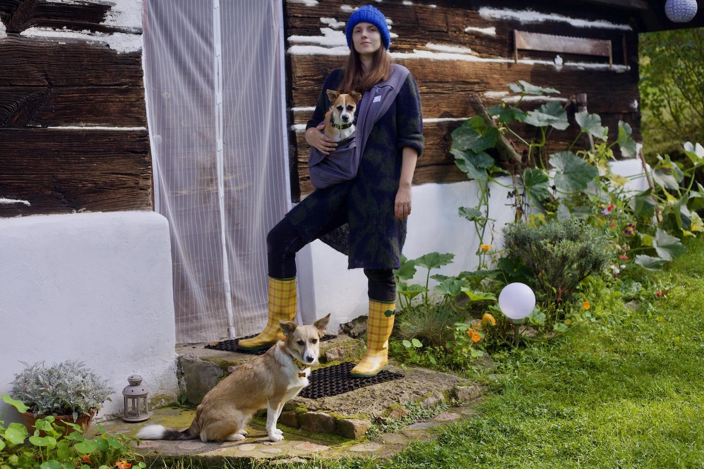 Dziewczyna w swetrze, kaloszach i czapce, z przewieszoną przez ramię szarą torbą, trzyma w środku niej małego pieska. Wystaje mu sama głowa. Na ziemi siedzi drugi pies.